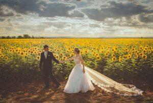 Bruid en bruidegom in veld zonnebloemen Foto door Ivan Cabanas via Unsplash