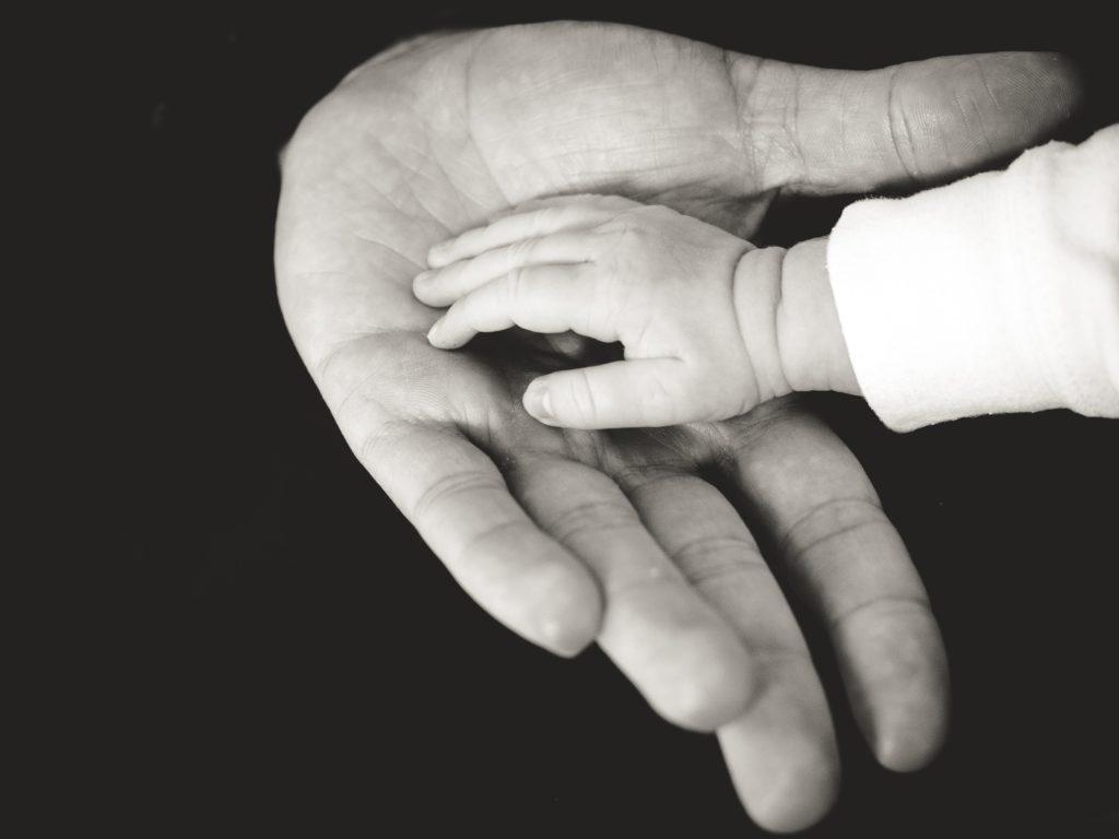 Hand volwassen man met kinderhand erin