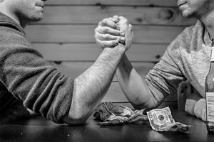 Image of two men arm wrestling with a few dollar bills on the table