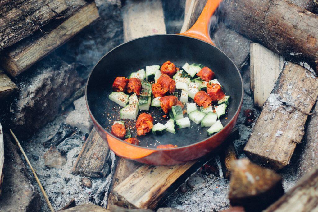 Foto van koekenpan met groente op open vuur