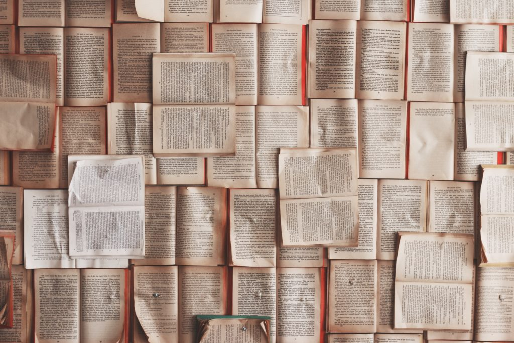 Foto van allemaal op elkaar en naast elkaar liggende pagina's met teksten uit een boek
