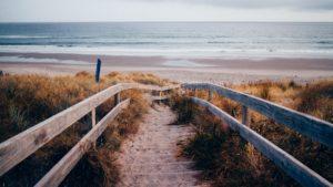 Foto van houten trap die naar een verlaten strand leidt