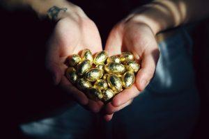 Extended hands full of Easter Eggs in gold wrapper